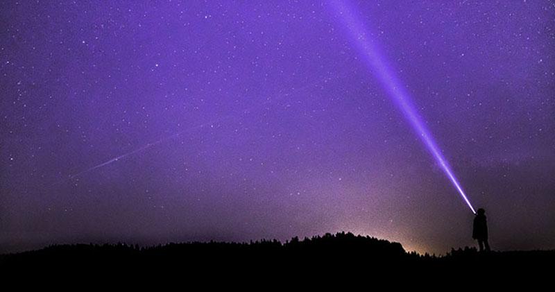 En person som står under en stjärnhimmel och lyser med en ficklampa.