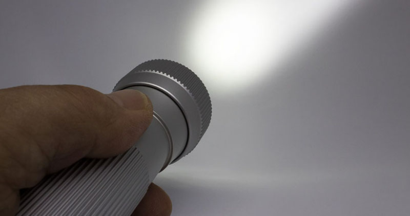 En person som lyser med en ficklampa.