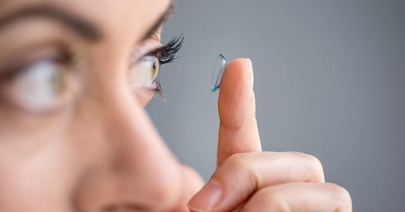 En kvinna som stoppar i en lins i ögat.