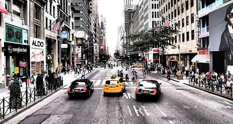 Tre bilar som kör på en gata i New York.
